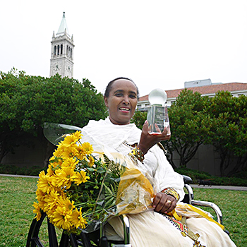 Berhane with her award, flowers from E&E RPCVs and the bell tower behind her.