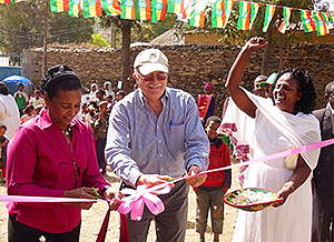 Ribbon cutting at opening of kindergarten from left: Elizabeth, Rick, and a member of the school organizing committee.