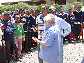Students stand at assembly welcoming the return of one of the first PCVs to expand the school to the secondary level