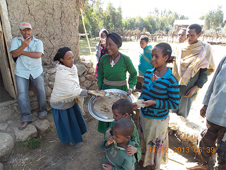 A local farmer (in green dress) shares locally produced injera where a key ingredient is fresh from the field potatoes near Debra Tabor. She learned, presumably via mobile phone, that the team was on the way to her farm and was able to whip up a batch of potato infused injera for the team. Ato Alemu, far left, from ARARI.