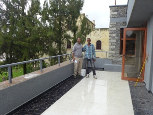 Building contractor, Negus, and Library manager, Arefaine, stand on the balcony of the new building with a glimpse of the old library in the background.
